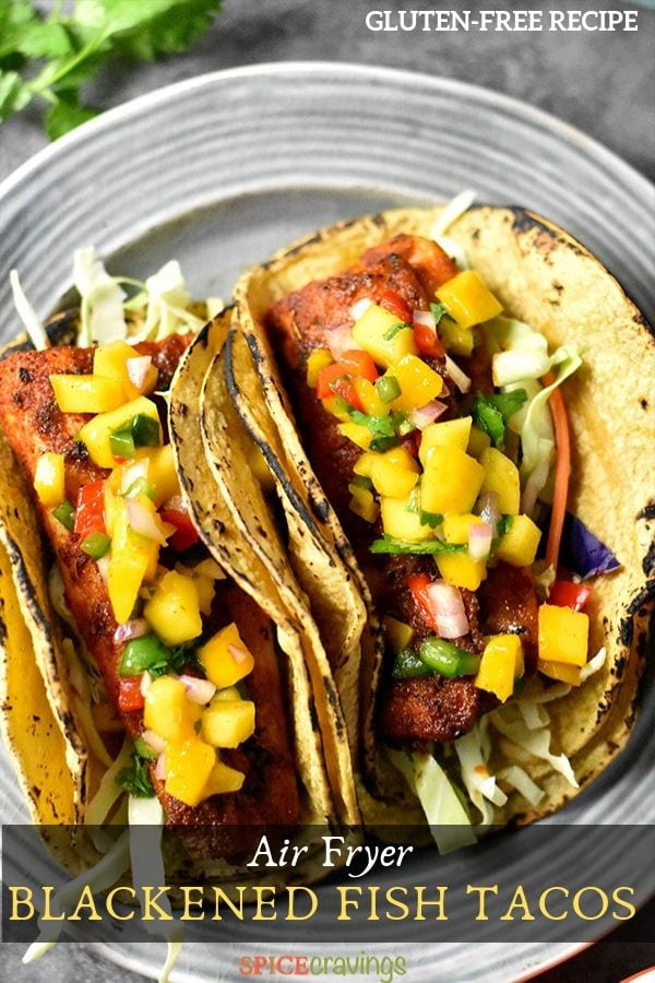 Two grilled fish tacos on a plate garnished with mango salsa