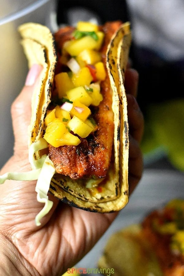 Blackened fish taco garnished with cabbage and mango salsa