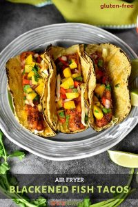 Three grilled fish tacos on a plate garnished with mango salsa