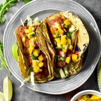 Two Grilled Fish Tacos garnished with fresh mango salsa