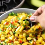 Scooping mango salsa with blue corn tortilla chip