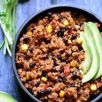 Quinoa burrito bowl with cilantro and avocado on the side