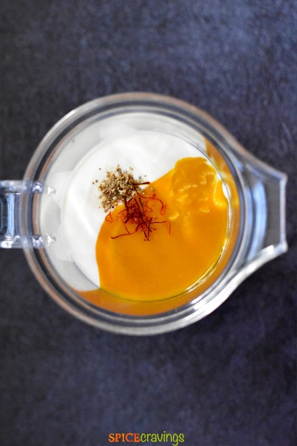 Yogurt, mango pulp, saffron and cardamom in a blender jar to make mango lassi