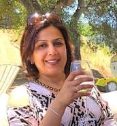 Aneesha holding a glass of white wine
