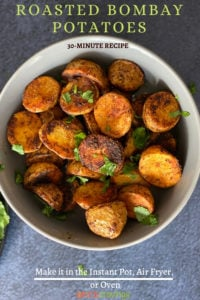 A bowl of crisp roasted bombay potatoes garnished with cilantro
