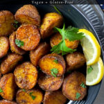 A bowl of spicy bombay potatoes with a garnish of lemon and cilantro