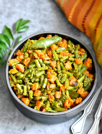 Green beans and carrots with coconut served with curry leaves in the backdrop