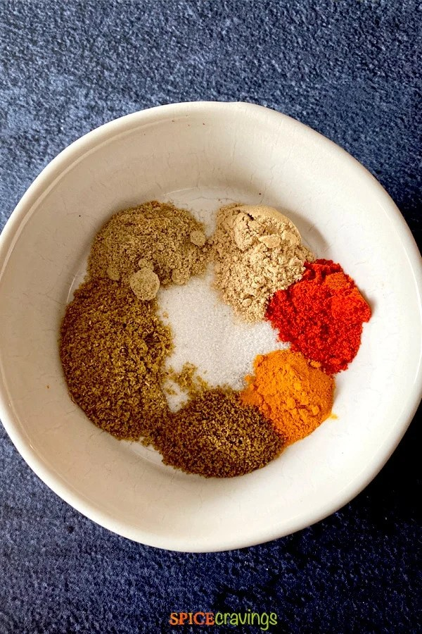 A bowl with assorted Indian spices for making Bombay Potatoes.