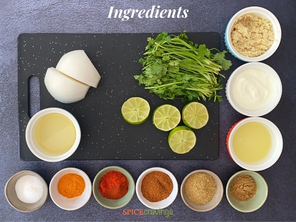 Ingredients for making Whole Tandoori Chicken spread out on a black cutting board