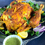 A whole roasted Chicken on a grey platter with green chutney