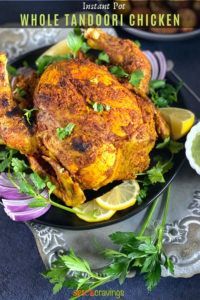 Crisp tandoori Chicken on a grey platter with lime and cilantro