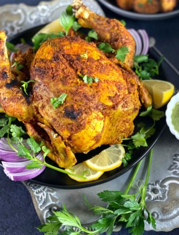 A whole roasted Tandoori Chicken on a grey platter