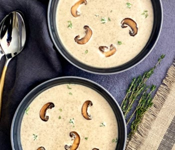 Two bowls with cream of mushroom soup garnished with thyme