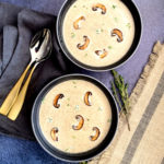 Two bowls with cream of mushroom soup with thyme