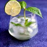 low carb mojito in cocktail glass garnished with lime slice and mint leaves with blue background