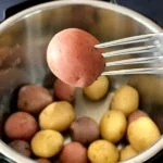 fork holding baby red potato over Instant pot with baby potatoes