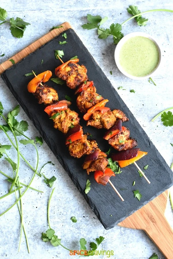 Two skewers of chicken tikka served on a gray slate