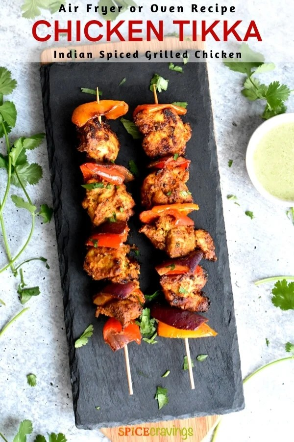 Two skewers of grilled Indian Chicken tikka on a slate tray
