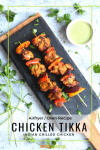 Two skewers of Chicken Tikka served on a slate tray