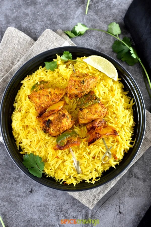 A bowl of Saffron rice with grilled chicken skewers on top