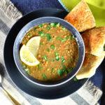 zesty instant pot lentil soup in gray bowl garnished with lemon slices and pita bread on side
