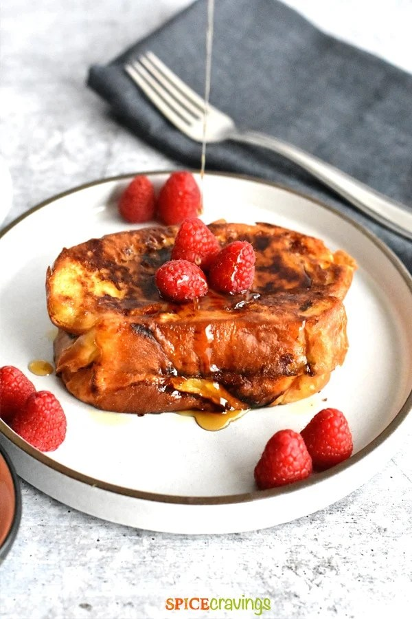 maple syrup drizzling on nutella french toast and berries on white plate with fork on blue napkin