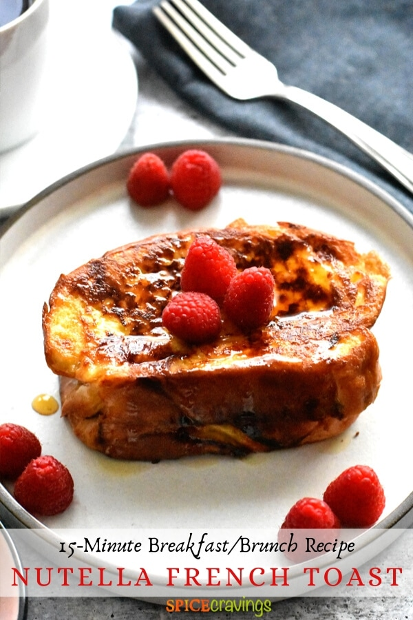 french toast with nutella on white plate with maple syrup and berries with fork on blue napkin