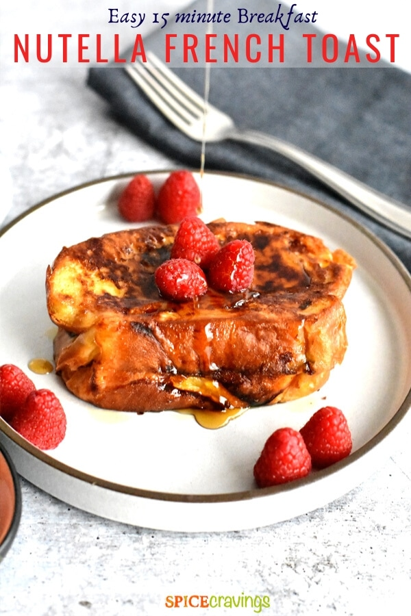 nutella french toast topped with maple syrup and berries on white plate with fork on blue napkin