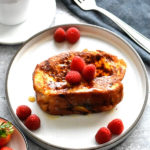nutella french toast topped with maple syrup and berries on white plate with mug of coffee