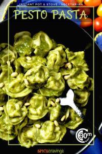tortellini pesto pasta in black bowl with fork garnished with pine nuts