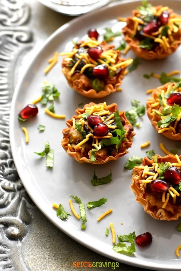 samosa chaat phyllo cups garnished with cilantro, pomegranate seeds and thin sev on white plate