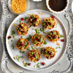 samosa chaat phyllo cups garnished with cilantro, pomegranate seeds and thin sev on white plate with chutneys in small bowls