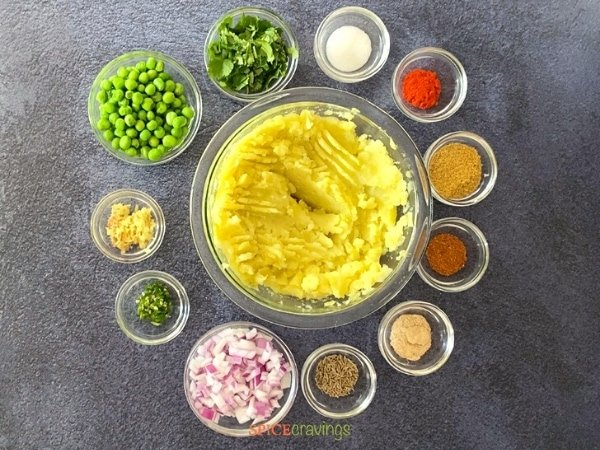 mashed potatoes in large glass bowl with peas, onions and spices in small glass bowls in a circle