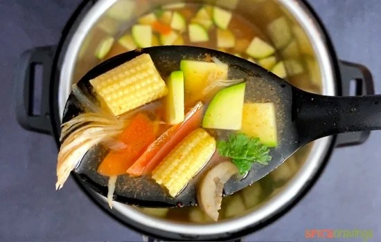 A ladle with Tom Yum Soup with baby corn, zucchini, carrots and chicken