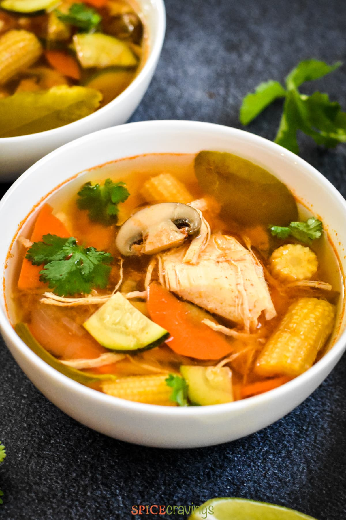 A bowl of tom yum soup with chicken, mushrooms and baby corn