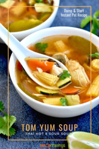 A bowl of thai tom yum soup with baby corn, chicken and carrots