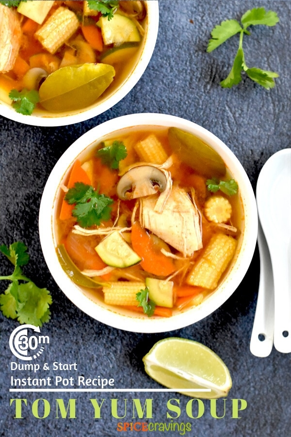 Tom yum soup in a white bowl with lime and cilantro on the side
