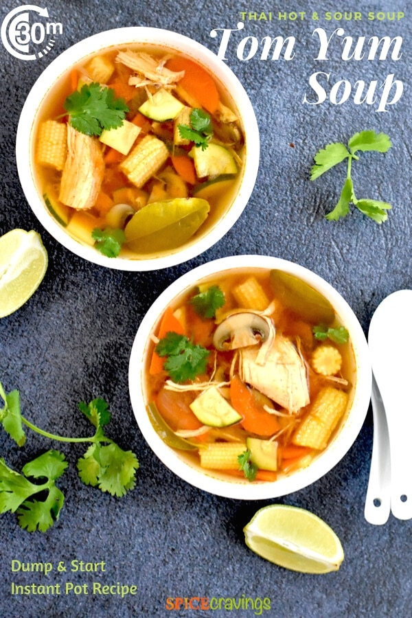 Two white bowls of Thai Tom Yum Soup, with lime and cilantro as garnishes