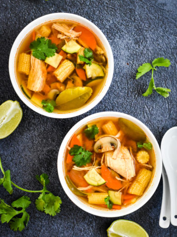 Two bowls of Thai Tom Yum Soup with mushroom, chicken and carrots.