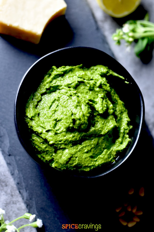 pesto recipe in black bowl with pine nuts, cheese, lemon and basil stems