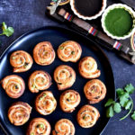 puff pastry samosa pinwheels on black serving plate with cilantro and tamarind chutney in two small white bowls