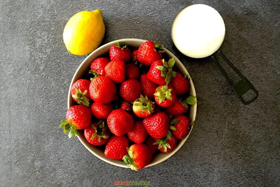 fresh strawberries in white bowl, lemon, sugar in measuring cup
