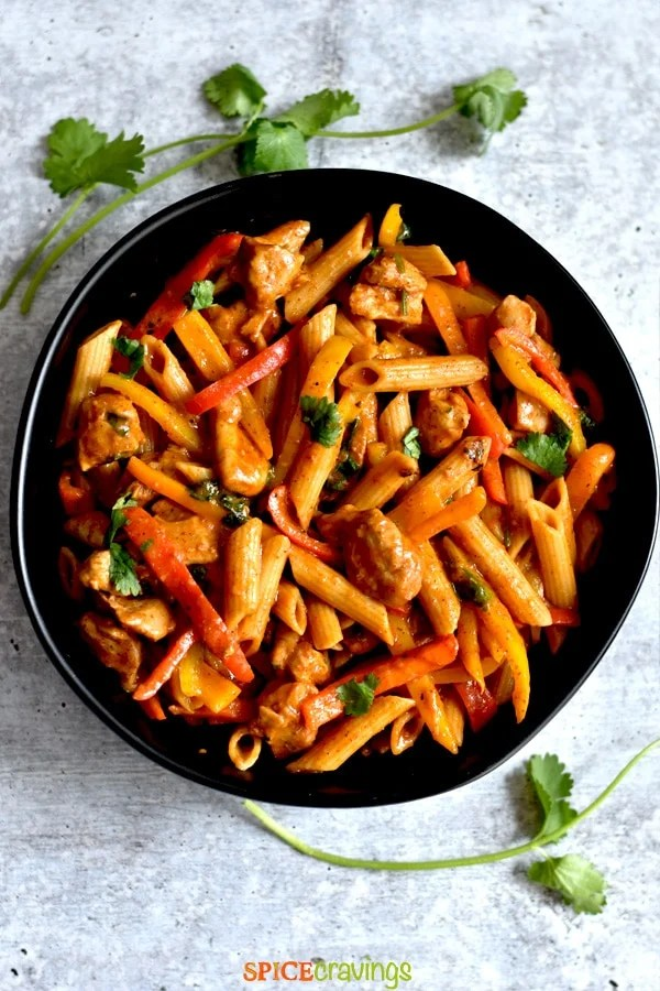 creamy chicken pasta with fajita vegetables in black bowl