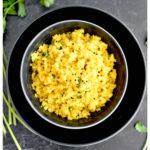 A bowl of yellow masala cauliflower rice in a grey dish