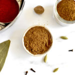 garam masala in small white bowl with ground Indian spices in backgroud