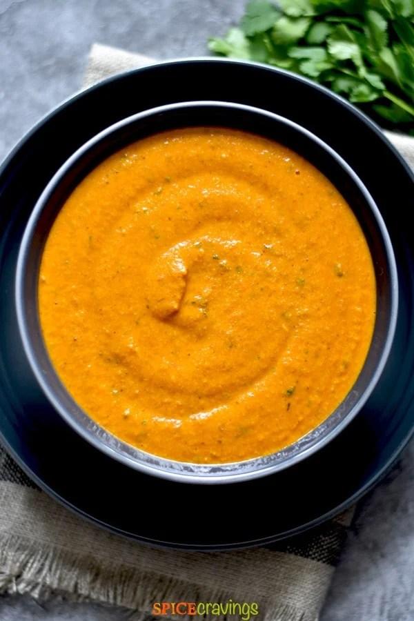 tikka masala sauce in gray bowl on navy blue plate