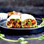 rice and black bean burrito on black plate with cilantro sprig