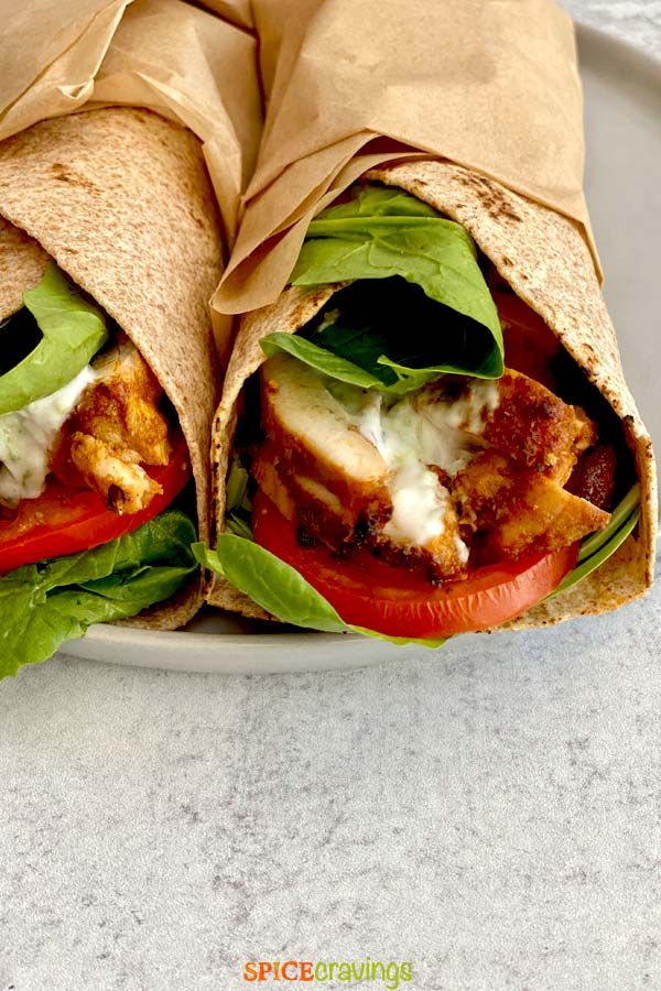 middle eastern chicken with lettuce, tomato and tzatziki in wrap