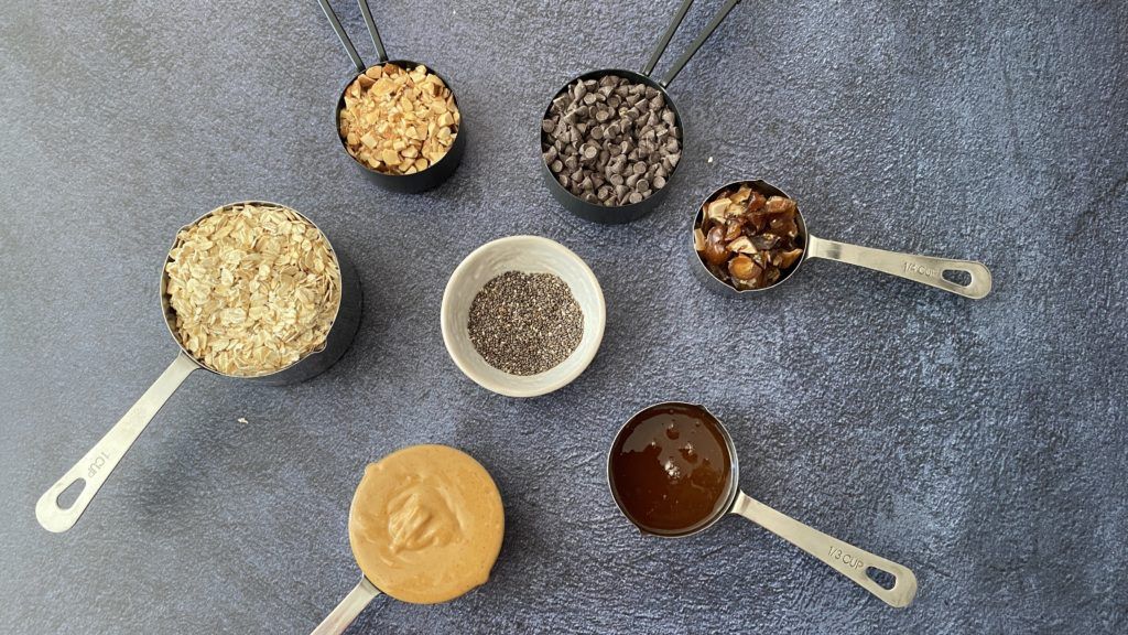 oats, peanut butter, honey, almonds, chia seeds, dates in measuring cups