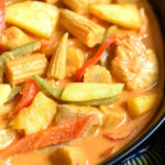 close-up of coconut chicken curry in black bowl